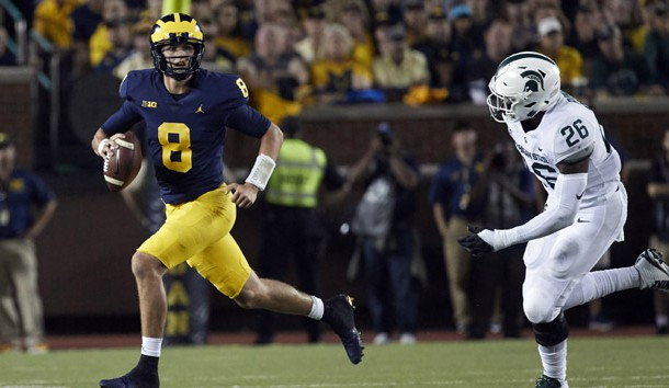 Oct 7, 2017; Ann Arbor, MI, USA; Michigan Wolverines quarterback John O'Korn (8) scrambles away from Michigan State Spartans defensive end Brandon Randle (26) in the first half at Michigan Stadium. Photo Credit: Rick Osentoski-USA TODAY Sports