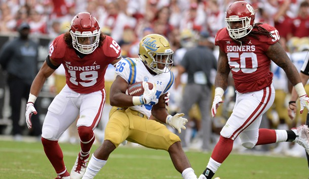 Sep 8, 2018; Norman, OK, USA; UCLA Bruins running back Martell Irby (26) runs against Oklahoma Sooners linebacker Caleb Kelly (19) and defensive tackle Arthur McGinnis (50) during the fourth quarter at Gaylord Family - Oklahoma Memorial Stadium. Photo Credit: Mark D. Smith-USA TODAY Sports