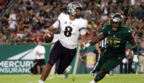 Nov 23, 2018; Tampa, FL, USA; UCF Knights quarterback Darriel Mack Jr. (8) runs out of the pocket as South Florida Bulls defensive tackle Brandon Boyce (95) pressures during the second half at Raymond James Stadium. Photo Credit: Kim Klement-USA TODAY Sports