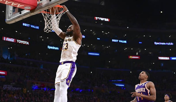 Dec 2, 2018; Los Angeles, CA, USA; Los Angeles Lakers forward LeBron James (23) slam dunks in the third quarter against the Phoenix Suns at Staples Center.Right is Phoenix Suns guard De'Anthony Melton (14). Photo Credit: Robert Hanashiro-USA TODAY Sports