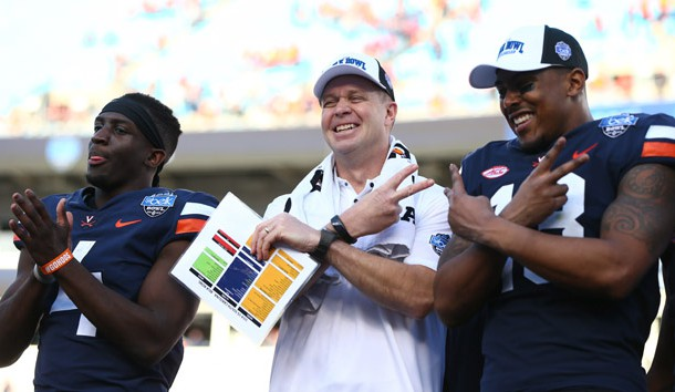 Dec 29, 2018; Charlotte, NC, USA; Virginia Cavaliers head coach Bronco Mendenhall wide receiver Olamide Zaccheaus (4) and wide receiver Ben Hogg (18) pose for a picture after defeating the South Carolina Gamecocks in the 2018 Belk Bowl at Bank of America Stadium. Photo Credit: Jeremy Brevard-USA TODAY Sports