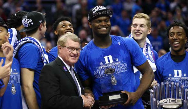Mar 16, 2019; Charlotte, NC, USA; ACC Commissioner John Swofford presents Duke Blue Devils forward Zion Williamson (1) with the tournament MVP trophy in the ACC conference tournament at Spectrum Center. Photo Credit: Jeremy Brevard-USA TODAY Sports